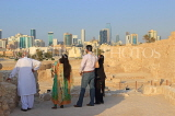 BAHRAIN, Manama, Karababad, Bahrain Fort (Qal'at al Bahrain), visitors, Manama skyline, BHR658JPL