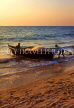 India, GOA, fishermen pushing boat out to sea, at dusk, IND664JPL