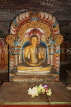 SRI LANKA, Dambulla Cave Temple (Golden Temple), Buddha statue in cave and flower offerings, SLK2775JPL