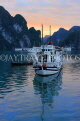 VIETNAM, Halong Bay, dawn, limestone formations and moored cruise boats, VT1823JPL