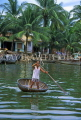 VIETNAM, Hoi An, Thu Bon River, man in small boat and riverside houses, VT155JPL